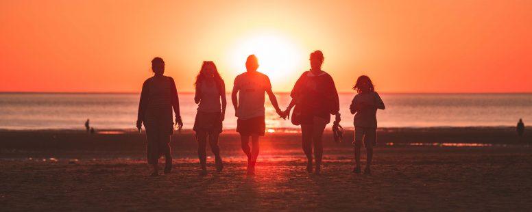 Familia anfitriona está caminando en la playa