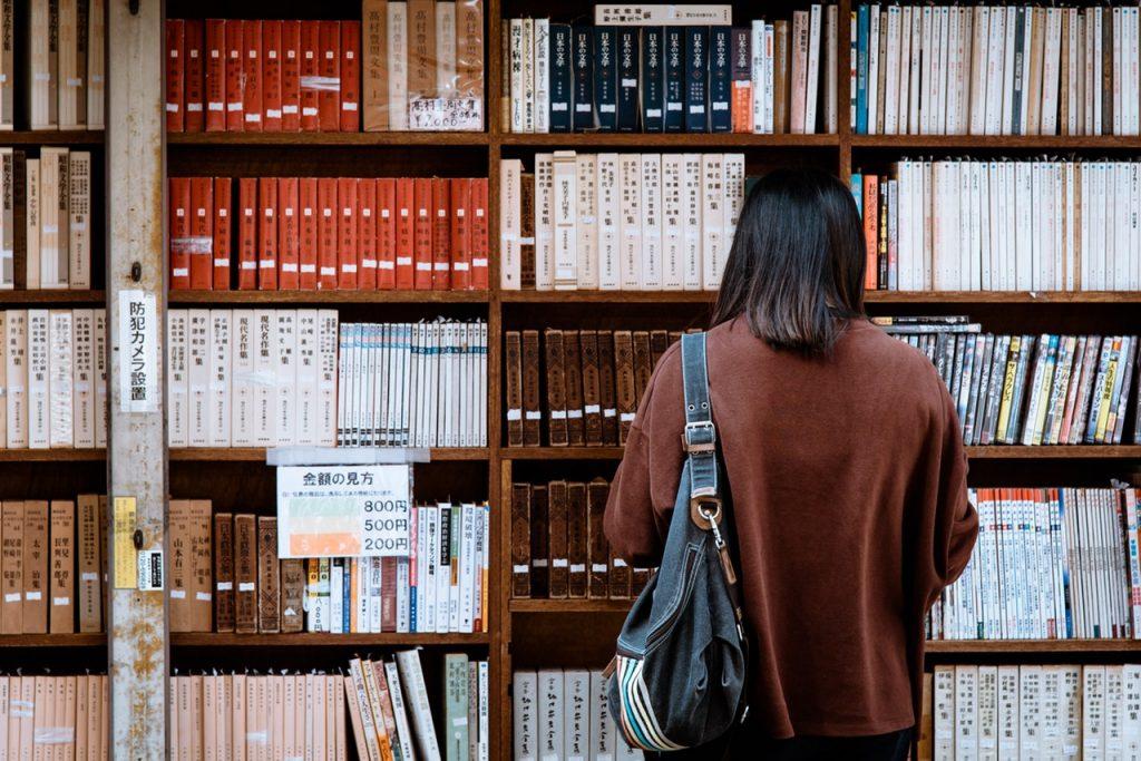 Chica en la biblioteca leyendo el libro japonés