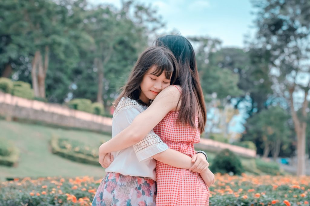 Dos chicas se están abrazando - dar hospedaje a una persona