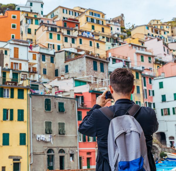 Young man traveling through Europe and taking picture, Cinque Terre, Italy