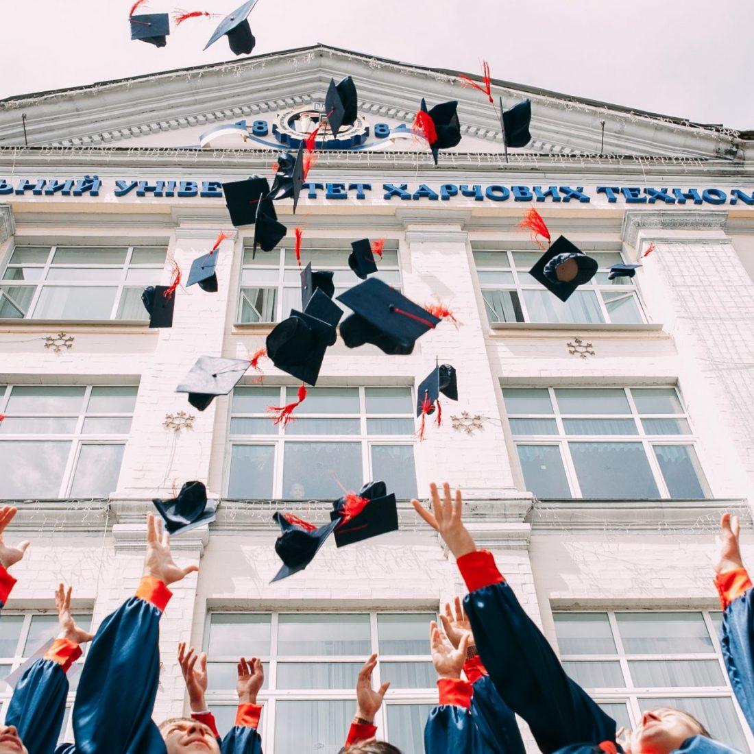 Estudiantes arrojando sombreros en el aire
